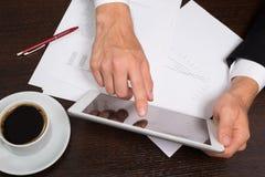 Επιχειρηματίας που γράφει σε χαρτί δίπλα στην ταμπλέτα, καφές, τηλέφωνο κυττάρων Στοκ φωτογραφία με δικαίωμα ελεύθερης χρήσης