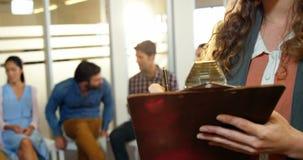Επιχειρηματίας που γράφει στην περιοχή αποκομμάτων ενώ συνάδελφοι που συζητούν στο υπόβαθρο απόθεμα βίντεο