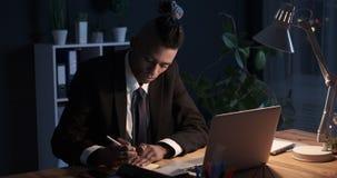 Επιχειρηματίας που γράφει στη συγκολλητική σημείωση και που κολλά την στο γραφείο lap-top τη νύχτα απόθεμα βίντεο