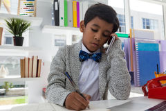 Επιχειρηματίας που γράφει στο βιβλίο μιλώντας στο κινητό τηλέφωνο Στοκ Φωτογραφίες