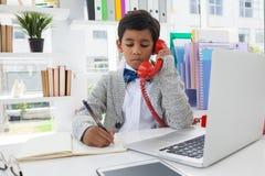 Επιχειρηματίας που γράφει στο βιβλίο μιλώντας στο τηλέφωνο γραμμών εδάφους Στοκ Εικόνες