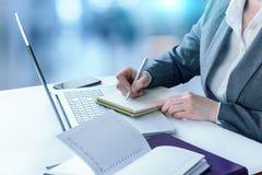 Επιχειρηματίας που γράφει στο γραφείο στην αρχή Στοκ φωτογραφία με δικαίωμα ελεύθερης χρήσης