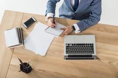 Επιχειρηματίας που γράφουν στο σημειωματάριο στον εργασιακό χώρο με το lap-top και έγγραφα στην αρχή Στοκ Φωτογραφίες