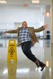 Επιχειρηματίας που γλιστρά στο υγρό πάτωμα Στοκ φωτογραφία με δικαίωμα ελεύθερης χρήσης