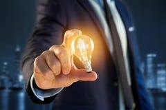 Επιχειρηματίας που δίνει μια ιδέα λαμπτήρων βολβών στο γραφείο Στοκ Εικόνα