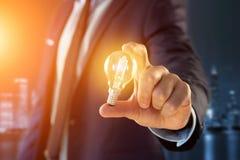 Επιχειρηματίας που δίνει μια ιδέα λαμπτήρων βολβών στο γραφείο Στοκ φωτογραφία με δικαίωμα ελεύθερης χρήσης