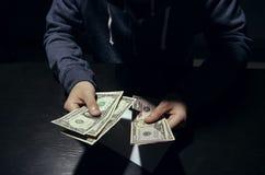 Επιχειρηματίας που δίνει τη απάτη δωροδοκίας χρημάτων τραπεζογραμματίων δωροδοκιών στο σκοτάδι στοκ εικόνες