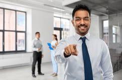 Επιχειρηματίας που δείχνει σας πέρα από τους ανθρώπους στην αρχή στοκ εικόνες