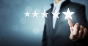 Επιχειρηματίας που δείχνει το πέντε αστέρων σύμβολο την εκτίμηση αύξησης του comp στοκ φωτογραφίες