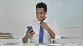 Επιχειρηματίας που διεγείρεται αφροαμερικανός για την επιτυχία χρησιμοποιώντας Smartphone φιλμ μικρού μήκους