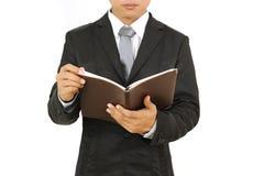 Επιχειρηματίας που δείχνει και που κρατά το βιβλίο σημειώσεων απομονωμένο στο άσπρο υπόβαθρο Στοκ φωτογραφία με δικαίωμα ελεύθερης χρήσης