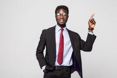 Επιχειρηματίας που δείχνει σε κάτι στο γκρίζο υπόβαθρο Στοκ φωτογραφία με δικαίωμα ελεύθερης χρήσης