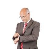 Επιχειρηματίας που δείχνει σε Wristwatch κοιτάζοντας μακριά Στοκ Φωτογραφίες