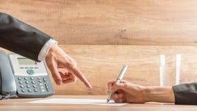 Επιχειρηματίας που δείχνει στη σύμβαση πού να υπογράψει Στοκ Εικόνες
