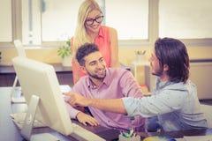 Επιχειρηματίας που δείχνει στον υπολογιστή ως χαμογελώντας συνάδελφοι που εξετάζουν το Στοκ Φωτογραφία