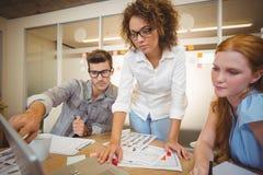 Επιχειρηματίας που δείχνει στο lap-top ως γυναίκα συνάδελφοι που εξετάζει το Στοκ φωτογραφίες με δικαίωμα ελεύθερης χρήσης