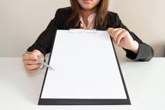 Επιχειρηματίας που δείχνει τα κενά έγγραφα σχετικά με το γραφείο της Στοκ Εικόνες