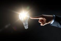 Επιχειρηματίας που δείχνει το δάχτυλο το lightbulb πέρα από το σκοτάδι Στοκ Φωτογραφίες