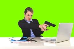 Επιχειρηματίας που δείχνει το πυροβόλο όπλο τη συνεδρίαση lap-top υπολογιστών στο πράσινο κλειδί χρώματος γραφείων Στοκ φωτογραφία με δικαίωμα ελεύθερης χρήσης