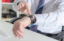 Επιχειρηματίας που δείχνει το ρολόι του με το δάχτυλό του Στοκ Εικόνες