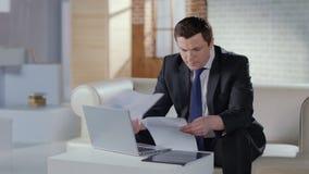 Επιχειρηματίας που ελέγχει τα έγγραφα στην αρχή, διάσκεψη Ιστού στο lap-top απόθεμα βίντεο