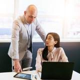 Επιχειρηματίας που εντυπωσιάζεται με την εργασία που γίνεται από τη γυναίκα υπάλληλός του Στοκ Φωτογραφία