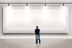 Επιχειρηματίας που εξετάζει έναν κενό πίνακα διαφημίσεων Στοκ Εικόνες