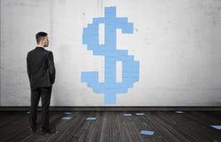 Επιχειρηματίας που εξετάζει τα μπλε φύλλα του εγγράφου που διαμορφώνει το μεγάλο σημάδι δολαρίων στον άσπρο τοίχο Στοκ εικόνα με δικαίωμα ελεύθερης χρήσης