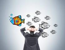 Επιχειρηματίας που εξετάζει τα ψάρια στον γκρίζο τοίχο στοκ εικόνα με δικαίωμα ελεύθερης χρήσης