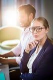 Επιχειρηματίας που εξετάζει τη κάμερα ενώ ο συνάδελφός της που εργάζεται στο υπόβαθρο Στοκ εικόνα με δικαίωμα ελεύθερης χρήσης
