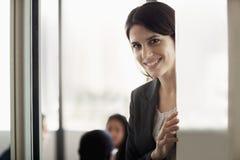 Επιχειρηματίας που εξετάζει τη κάμερα και που χαμογελά κατά τη διάρκεια μιας επιχειρησιακής συνεδρίασης Στοκ Εικόνες