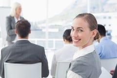 Επιχειρηματίας που εξετάζει τη κάμερα κατά τη διάρκεια της συνεδρίασης Στοκ Εικόνες