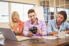 Επιχειρηματίας που εξετάζει τη κάμερα με την εργασία συναδέλφων Στοκ εικόνα με δικαίωμα ελεύθερης χρήσης