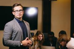 Επιχειρηματίας που εξετάζει τη κάμερα με τους θολωμένους εργαζομένους στο υπόβαθρο Στοκ Φωτογραφίες