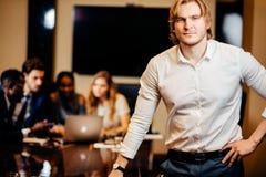 Επιχειρηματίας που εξετάζει τη κάμερα με τους θολωμένους εργαζομένους στο υπόβαθρο Στοκ Εικόνες