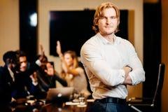 Επιχειρηματίας που εξετάζει τη κάμερα με τους θολωμένους εργαζομένους στο υπόβαθρο Στοκ φωτογραφία με δικαίωμα ελεύθερης χρήσης
