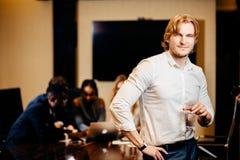 Επιχειρηματίας που εξετάζει τη κάμερα με τους θολωμένους εργαζομένους στο υπόβαθρο Στοκ εικόνες με δικαίωμα ελεύθερης χρήσης