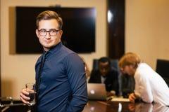 Επιχειρηματίας που εξετάζει τη κάμερα με τους θολωμένους εργαζομένους στο υπόβαθρο Στοκ εικόνα με δικαίωμα ελεύθερης χρήσης