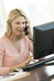 Επιχειρηματίας που εξετάζει τον υπολογιστή απαντώντας στο τηλέφωνο στο Ο Στοκ Εικόνες