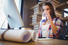 Επιχειρηματίας που εξετάζει τον υπολογιστή ενώ πόσιμο νερό Στοκ Φωτογραφίες