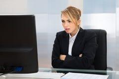 Επιχειρηματίας που εξετάζει τον υπολογιστή στην αρχή Στοκ Εικόνα