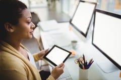 Επιχειρηματίας που εξετάζει τον υπολογιστή χρησιμοποιώντας την ψηφιακή ταμπλέτα στο δημιουργικό γραφείο Στοκ Εικόνες