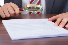 Επιχειρηματίας που εξετάζει το έγγραφο με την ενίσχυση - γυαλί Στοκ Εικόνα