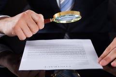 Επιχειρηματίας που εξετάζει το έγγραφο συμβάσεων με την ενίσχυση - γυαλί Στοκ Εικόνες