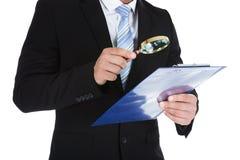 Επιχειρηματίας που εξετάζει το έγγραφο σχετικά με την περιοχή αποκομμάτων Στοκ Εικόνα