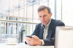 Επιχειρηματίας που εξετάζει το έξυπνο τηλέφωνο σε έναν καφέ Στοκ φωτογραφία με δικαίωμα ελεύθερης χρήσης