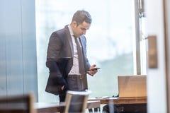 Επιχειρηματίας που εξετάζει το έξυπνο τηλέφωνο στο σύγχρονο εταιρικό γραφείο Στοκ εικόνα με δικαίωμα ελεύθερης χρήσης