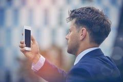 Επιχειρηματίας που εξετάζει το κινητό τηλέφωνο Στοκ εικόνα με δικαίωμα ελεύθερης χρήσης