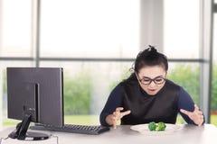 Επιχειρηματίας που εξετάζει το μπρόκολο στο πιάτο Στοκ Εικόνα