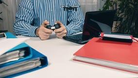 Επιχειρηματίας που εξετάζει το νέο παιχνίδι στο γραφείο στην αρχή Παιχνίδι γραφείων Στοκ Εικόνα